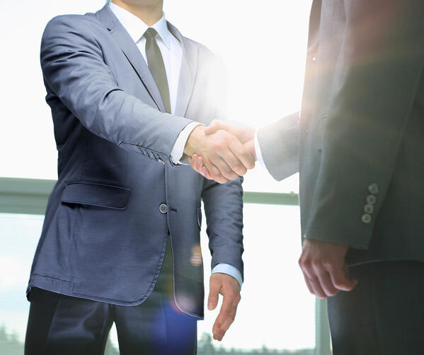 Two people shaking hands wearing suits