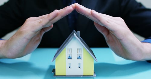 Hands covering a yellow model house