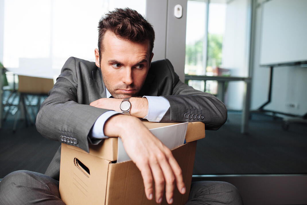 A sad man in a suit leaning on a box with his office supplies in it