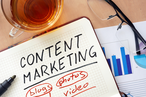 "Content marketing on whiteboard with the words ""blogs, photos, video"" written in red"
