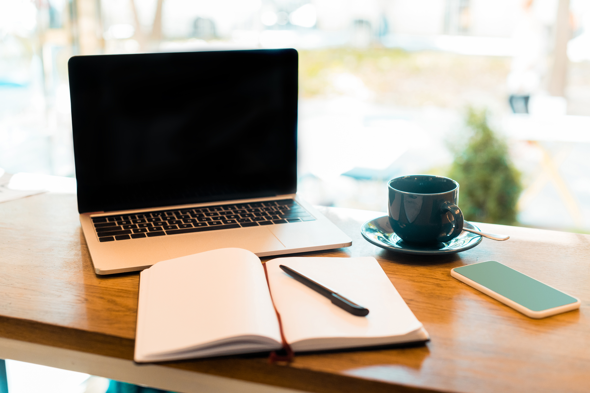 Laptop with blank screen, notebook and cup of tea on wooden cafe counter
