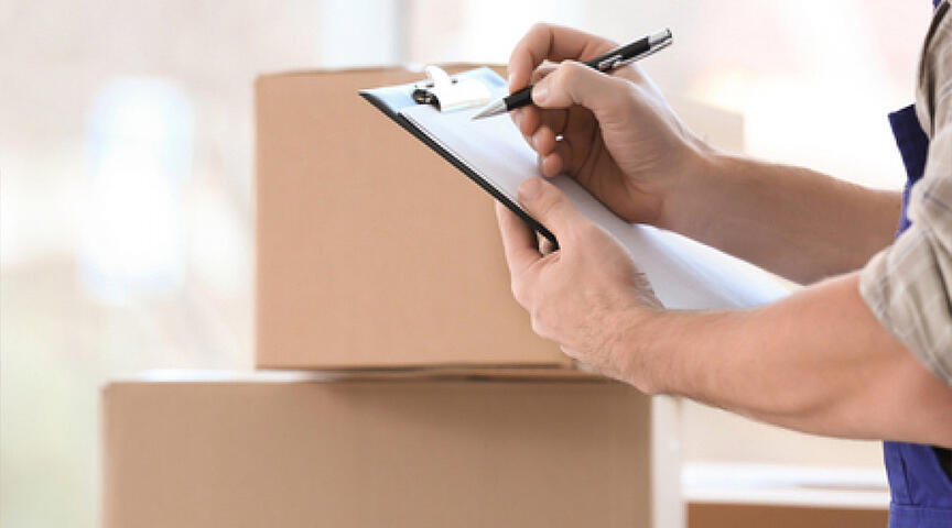 person checking off items on moving out to do list