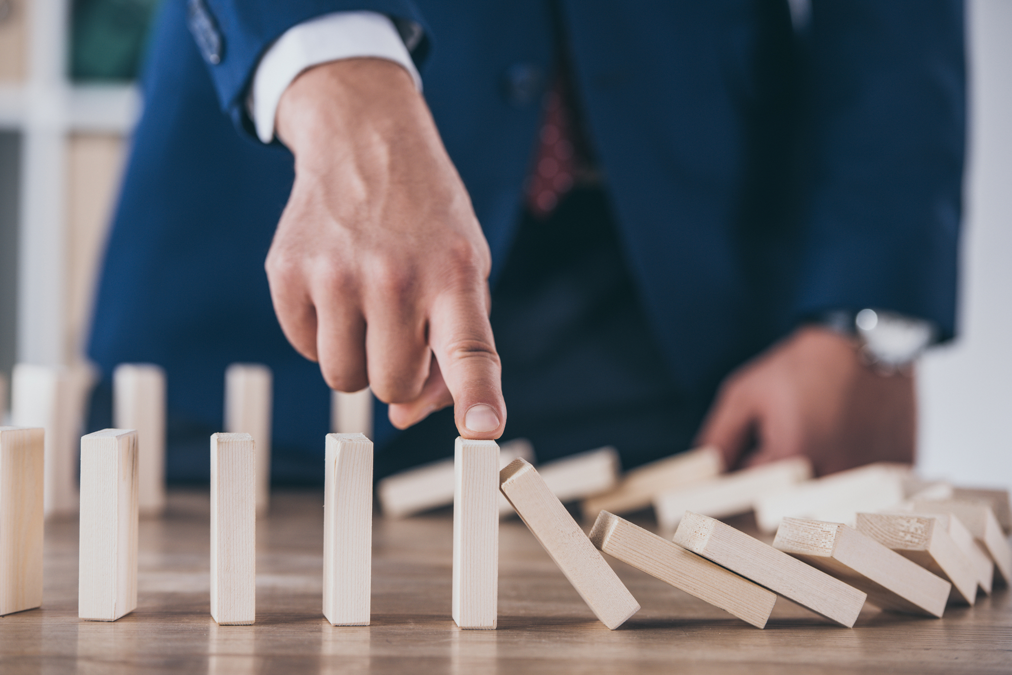 Partial view of risk manager blocking domino effect of falling wooden blocks-1