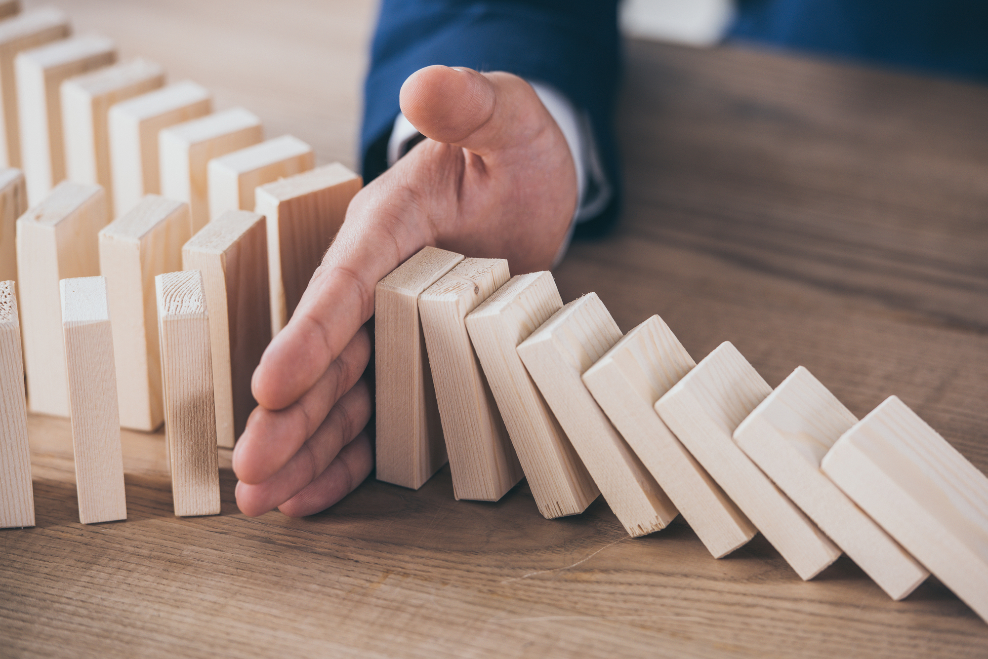 Partial view of risk manager blocking domino effect of falling wooden blocks