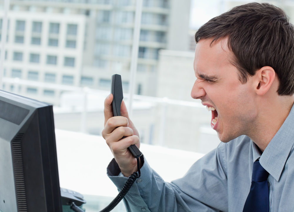 Angry office worker on the phone in his office