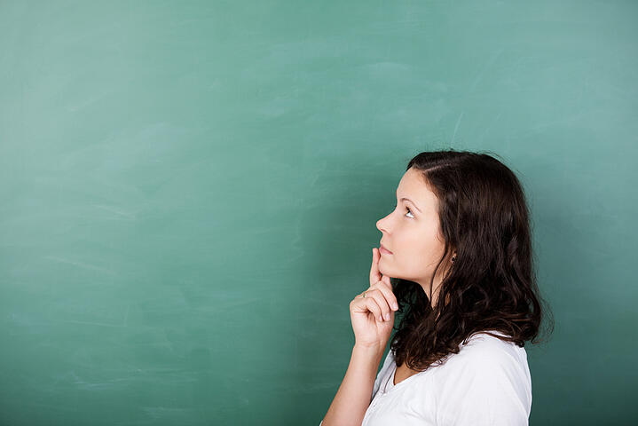Attractive young female student standing solving a problem staring thoughtfully up into the air with her finger to her lips against a blank green blackboard with copyspace