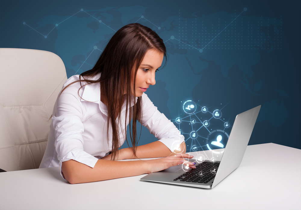 Beautiful young lady sitting at desk and typing on laptop with social network icons coming out.