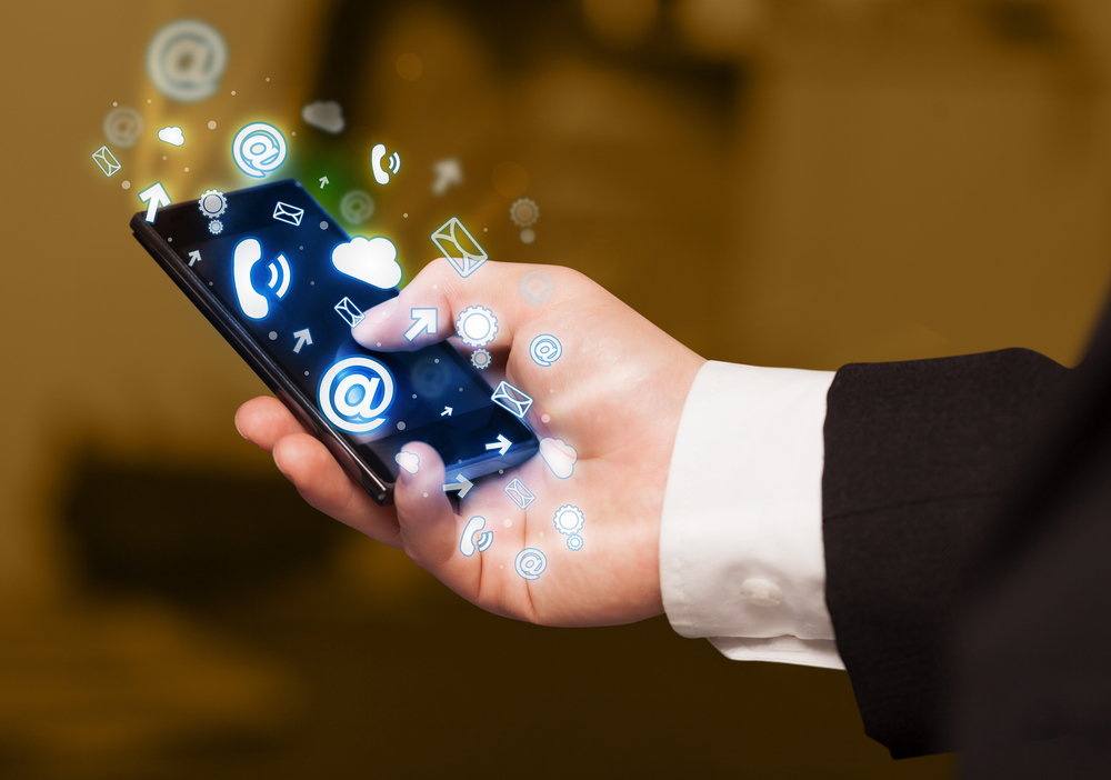 Business man holding smart phone with media icons concept on background