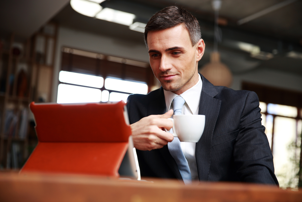 Businessman drinking coffee and reading news in cafe