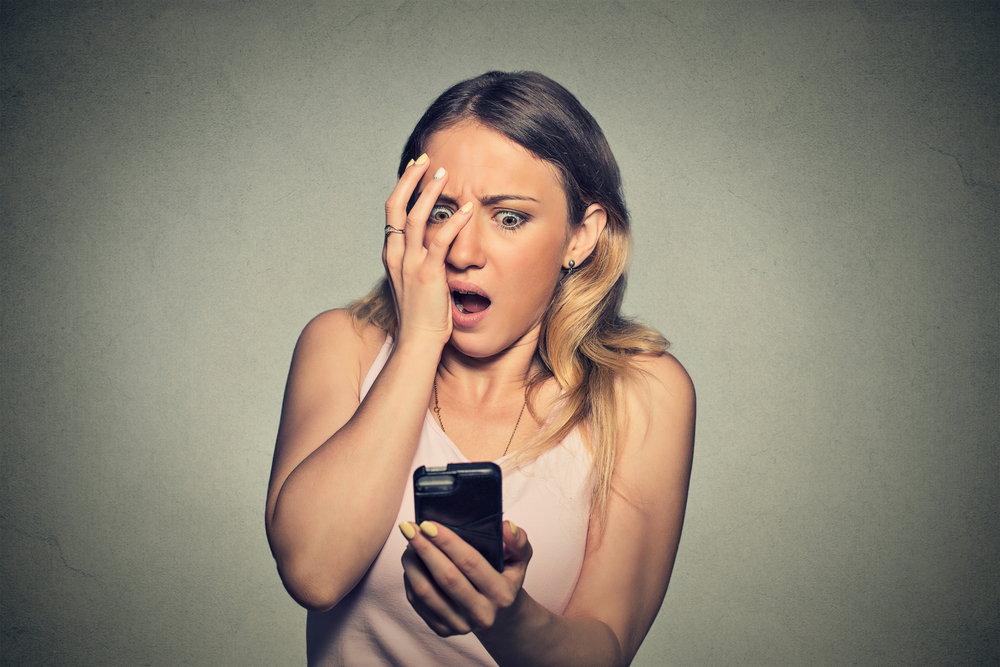 Closeup portrait anxious scared young girl looking at phone seeing bad news photos message with disgusting emotion on her face isolated on gray wall background. Human reaction, expression