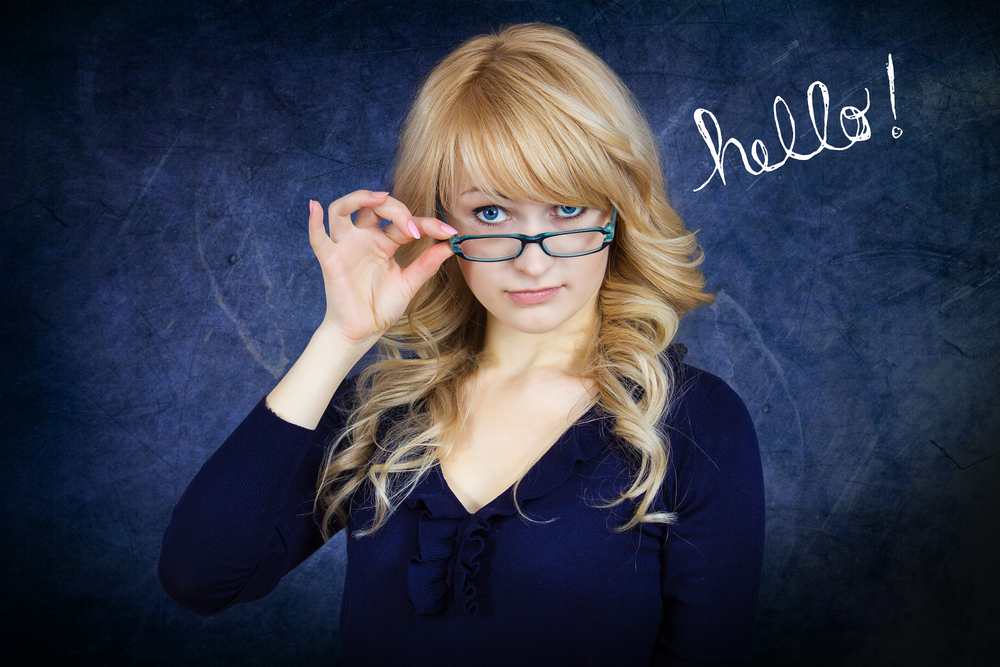 Closeup portrait young attractive woman with blue glasses peering above frames, flirting with you, isolated blue-gray background. Positive emotion facial expression feelings, attitude, body language