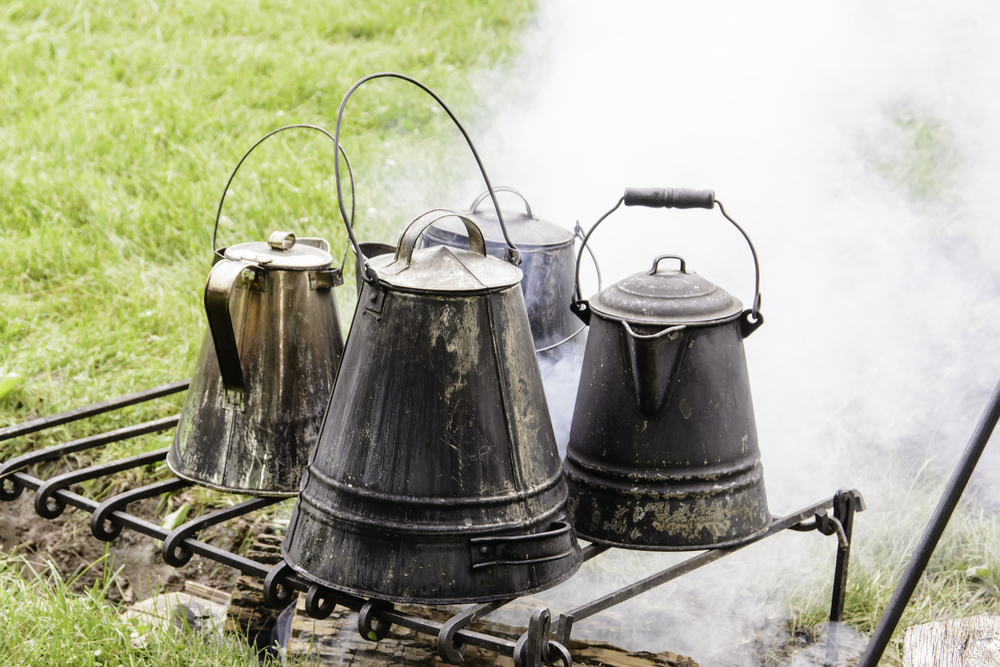 Four vintage coffeepots over a smoky campfire