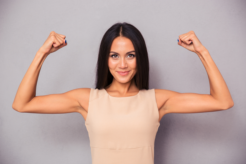 Portrait of a happy business woman showing her biceps on gray background