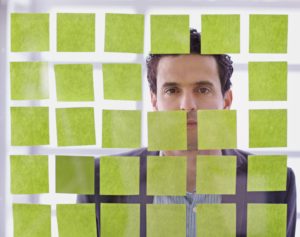 Portrait of a middle eastern business man behind sticky notes in bright glass office-1