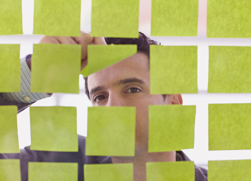 Portrait of a middle eastern business man behind sticky notes in bright glass office
