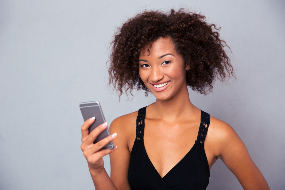 Portrait of a smiling afro american woman using smartphone over gray background