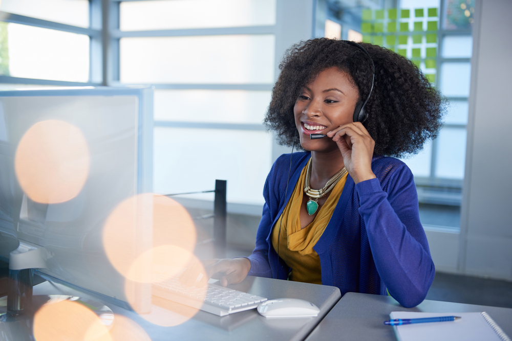 Portrait of a smiling customer service representative with an afro at the computer using headset-2