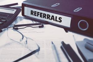 Referrals - Ring Binder on Office Desktop with Office Supplies. Business Concept on Blurred Background. Toned Illustration.