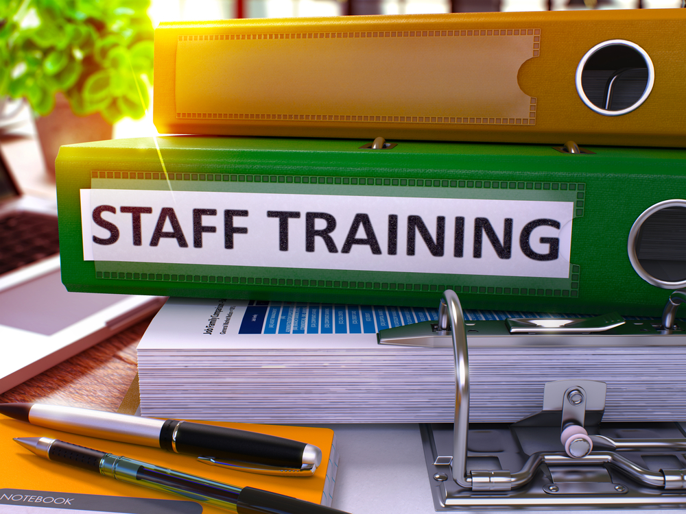 Staff Training - Green Office Folder on Background of Working Table with Stationery and Laptop. Staff Training Business Concept on Blurred Background. Staff Training Toned Image. 3D.-1