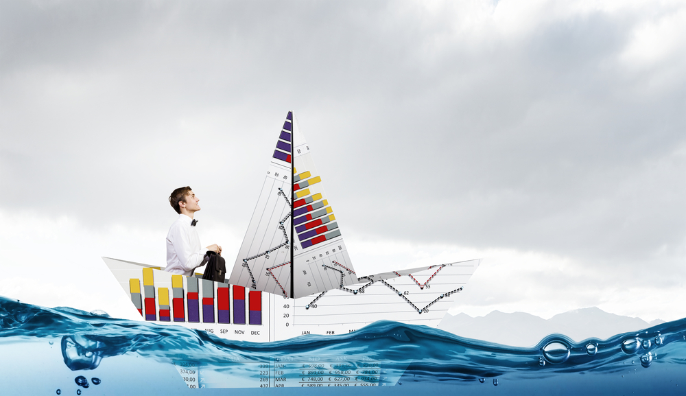Successful businessman sailing on paper boat in financial sea-1