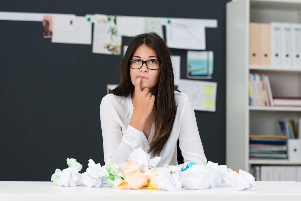 Young woman with writers block sitting in an office with a desk littered with crumpled paper as she sits looking thoughtfully into the air with her finger to her chin seeking new ideas
