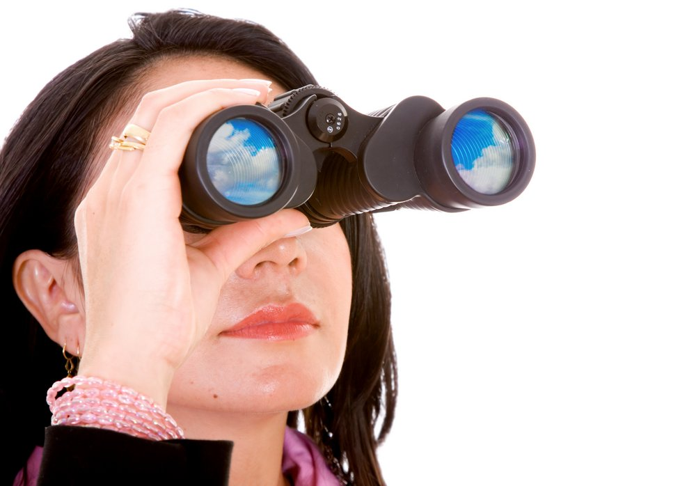 business woman doing a search with her binoculars - isolated over a white background