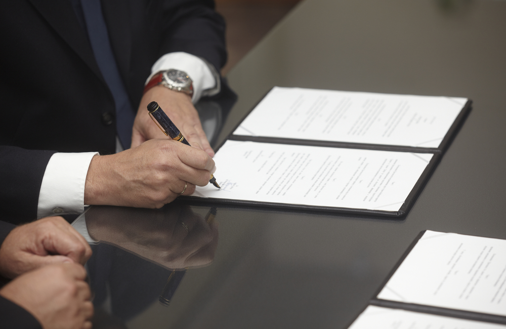 close up of businessman hands signing contract