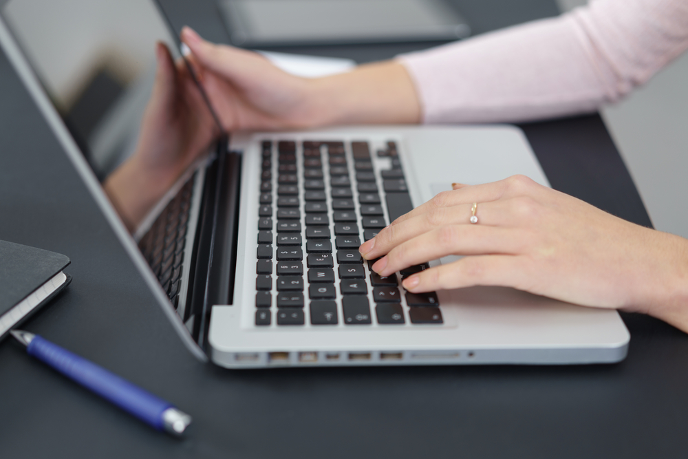 close-up of womans hands working on her laptop at the desk