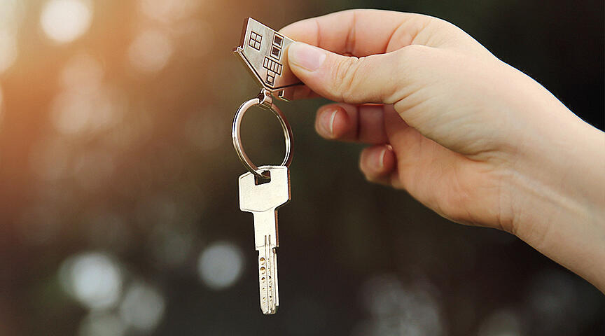 hand holding key to new rental property