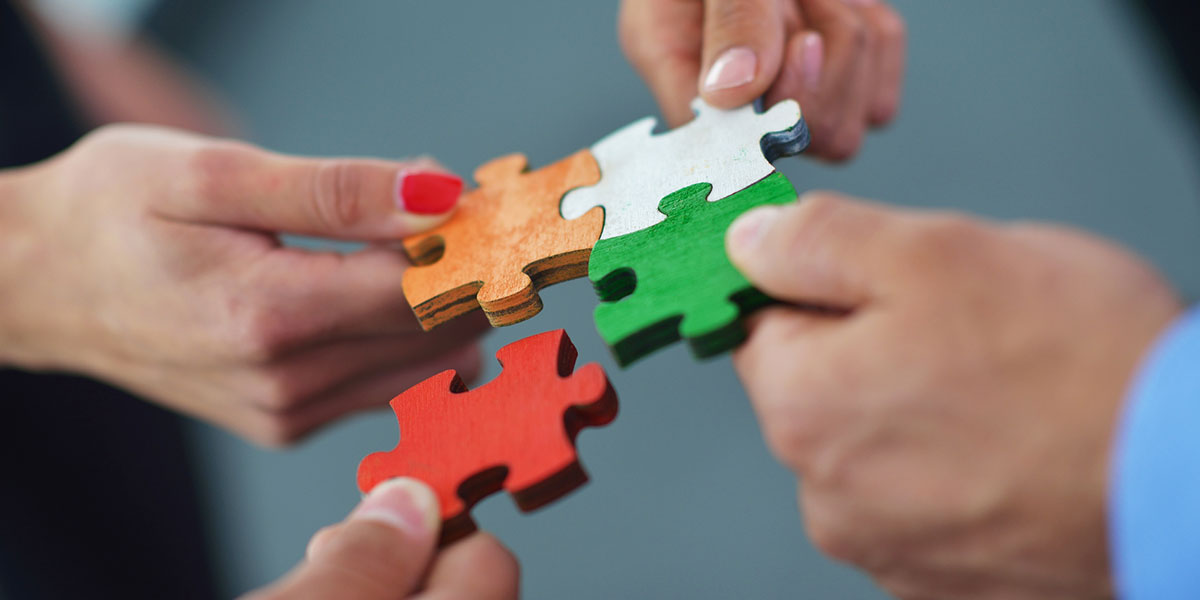 Four people putting their own different colored puzzle pieces together