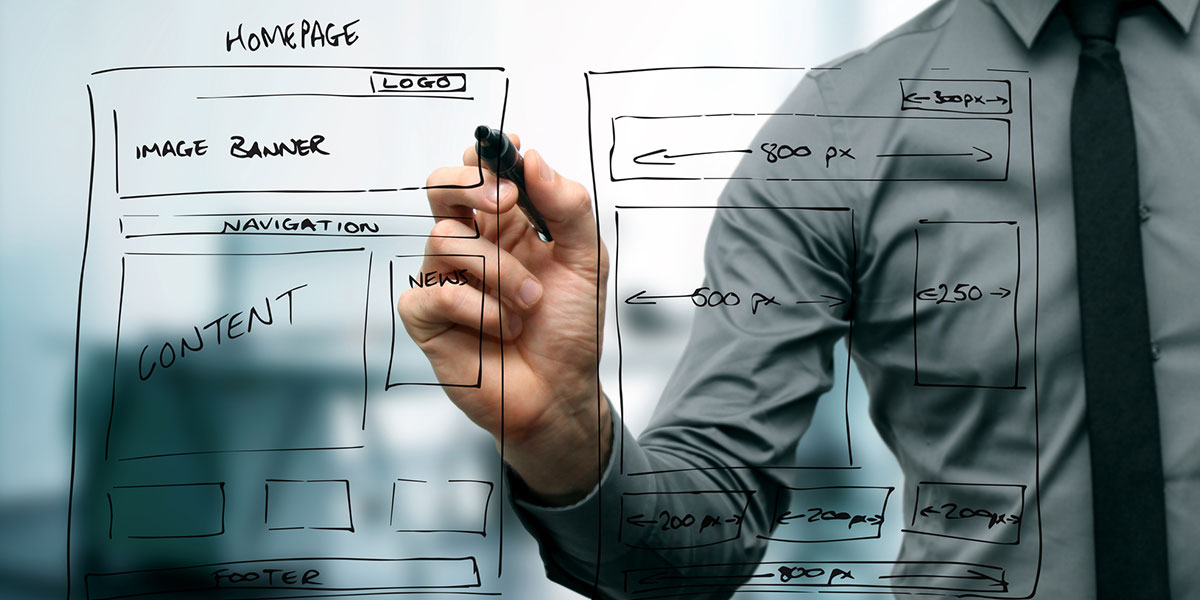 A person drawing website wireframes on a window or glass